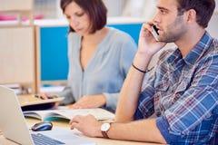 Equipe a fala no telefone com a mulher que trabalha no fundo Imagens de Stock