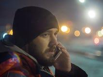Equipe a fala pelo smartphone na luz do bokeh da noite no fundo Conceito do turno da noite Fotografia de Stock Royalty Free