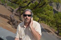 Equipe a fala pelo telefone no banco no parque Imagem de Stock Royalty Free