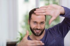 Equipe a fatura de um gesto do quadro com suas mãos Imagens de Stock