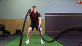 Equipe fazer exercícios com cordas durante o treinamento do crossfit no gym filme