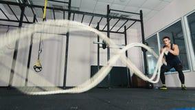 Equipe fazer o exercício de luta da corda no gym filme