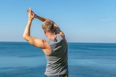 Equipe fazer um exercício do aquecimento no oceano Ar fresco e um estilo de vida saudável imagem de stock