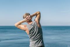 Equipe fazer um exercício do aquecimento no oceano Ar fresco e um estilo de vida saudável foto de stock