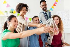 Equipe feliz com bebidas que comemora no partido de escritório Foto de Stock