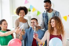 Equipe feliz com bebidas que comemora no partido de escritório Imagem de Stock Royalty Free
