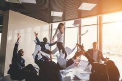 Equipe feliz do negócio que comemora a vitória no escritório suporte da mulher na tabela foto de stock