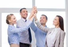 Equipe feliz do negócio que dá a elevação cinco no escritório Fotografia de Stock