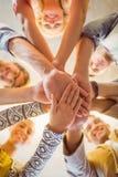 Equipe feliz do negócio que junta-se a suas mãos Fotografia de Stock Royalty Free