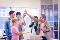 Equipe feliz do negócio que faz verificações das mãos Imagem de Stock Royalty Free