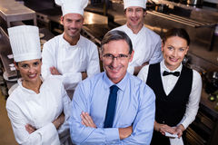 A equipe feliz do restaurante que está junto com os braços cruzou-se na cozinha comercial foto de stock