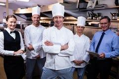 Equipe feliz do restaurante que está junto na cozinha comercial fotografia de stock royalty free