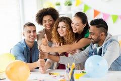 Equipe feliz no partido de escritório que mostra os polegares acima Imagem de Stock