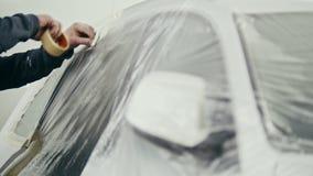 Equipe a fita adesiva da colagem na porta de carro automobilístico da pintura filme