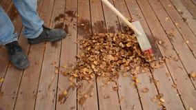 Equipe folha arrebatadora do outono no pátio de madeira em uma pilha grande filme