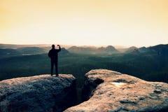 Equipe a fotografia com paisagem montanhosa sonhadora do phoneof, nascer do sol enevoado cor-de-rosa alaranjado da mola em um val Imagem de Stock Royalty Free