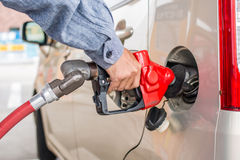 Equipe a gasolina de bombeamento da mão com o inseto em luzes do carro Imagem de Stock Royalty Free