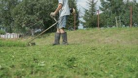 Equipe a grama do aparamento no jardim usando o lawnmower filme