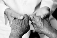 Equipe guardar as mãos de um homem superior Imagem de Stock Royalty Free