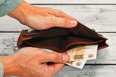 Equipe guardar a carteira quase vazia com dinheiro do russo fotografia de stock royalty free