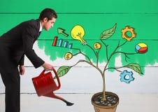 Equipe guardar a lata molhando e a tiragem de gráficos de negócio em ramos da planta na parede Fotos de Stock Royalty Free