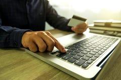 Equipe guardar o cartão de crédito e a utilização do portátil para a compra do pagamento sobre fotografia de stock royalty free