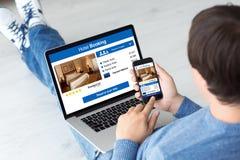 Equipe guardar o computador e o telefone com reserva de hotel do app Foto de Stock
