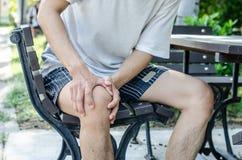 Equipe guardar o joelho direito com ambas as mãos ao sentar-se para baixo Imagem de Stock Royalty Free