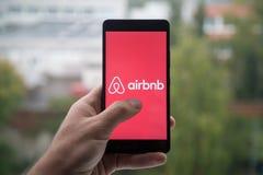 Equipe guardar o smartphone com logotipo de Airbnb com o dedo na tela foto de stock