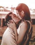 Equipe guardar sua esposa e a doação lhe de um beijo em um pH vermelho morno do tom imagens de stock