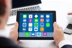 Equipe guardar a tabuleta com apps dos ícones da tela home sobre a tabela Fotografia de Stock