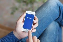 Equipe guardar um iPhone branco com App Facebook na tela Foto de Stock Royalty Free