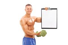 Equipe guardar um peso dos brócolis e uma prancheta Imagem de Stock Royalty Free