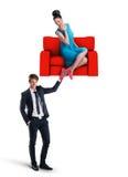 Equipe guardar um sofá com a mulher que senta-se nele Imagens de Stock Royalty Free