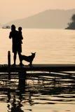 Equipe guardar uma criança no cais de madeira durante o por do sol com animal de estimação, Famil Fotos de Stock Royalty Free