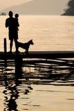 Equipe guardar uma criança no cais de madeira durante o por do sol com animal de estimação, Famil Imagem de Stock Royalty Free