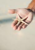 Guardarando uma estrela do mar Imagens de Stock Royalty Free