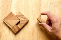 Equipe guardou a parte de enigma do tangram para cumprir a forma do coração Fotos de Stock