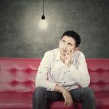 Equipe a ideia de pensamento no sofá quando olhar na lâmpada Fotografia de Stock Royalty Free