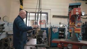 Equipe a instalação da caixa de engrenagens do kamaz em uma máquina aborrecida no serviço gasto velho do carro filme