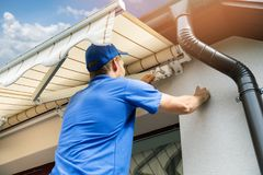 Equipe a instalação do toldo na parede da fachada da casa sobre o balcão foto de stock