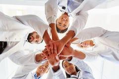 A equipe inter-racial da pilha dos doutores entrega junto Foto de Stock