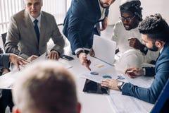Equipe inter-racial incorporada do negócio com líder alegre em uma reunião, fim acima imagens de stock