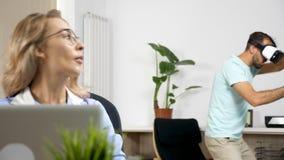 Equipe jogos da realidade virtual dos jogos na sala de visitas quando sua amiga tentar trabalhar no computador video estoque