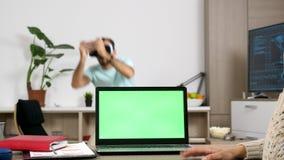 Equipe jogos de vídeo da realidade virtual dos jogos quando uma mulher na mesa olhar o computador verde da tela quando falando no filme