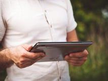 Equipe a leitura da tabuleta digital fora, perto acima fotografia de stock royalty free