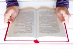 Equipe a leitura de um livro em um fundo de madeira branco Imagem de Stock