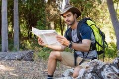 Equipe a leitura do mapa ao descansar na floresta imagens de stock