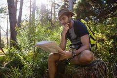 Equipe a leitura do mapa ao descansar no coto de árvore foto de stock