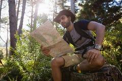 Equipe a leitura do mapa ao descansar no coto de árvore fotos de stock royalty free